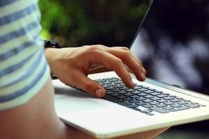 ręka mężczyzny nad laptopem